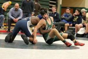 Dragon wrestler Nick Nowakowski (in green) grapples with an opponent during the team district wrestling competition Feb. 9. Photo by Darin Smith