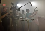 """Cinematographer Istvan Lettang films the scene as Director/Producer Sam Logan Khaleghi (center, white shirt) gives direction and calls for """"Action."""""""