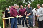 J.R. Nowells of Lake Orion Lumber cuts the ribbon during the Paint Creek Trail dedication ceremony during National Trails Day on Saturday. Lake Orion Lumber granted an easement through the lumberyard property, allowing construction of the trail.