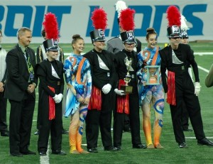LOHS band Director Michael Steele (from left) and Drum Majors Delany Carron, Emily Pauzus, Lauren Hough, Owen Kock, and Guard Captains Nicole Marion and Olivia Boullin accept their fourth place trophy. Photo courtesy of Pam Shuck