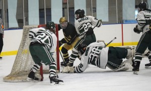 Lake Orion goalie Reid Marshall makes one of his 28 saves, diving backward to deny a Howell player a goal. That little black dot between Marshall's glove and the post is the puck. Photo by Jim Newell.