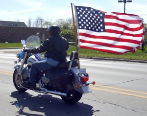 A motorcyclist flies the American Flag down Lapeer Rd.