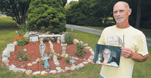 Christopher Woityra holds a photo his late daughter Taylor Beth as he stands near the memorial garden he created in the shape of a peace sign. Photo by C.J. Carnacchio.