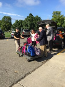 State Senator Jim Marleau, State Representative Bradford Jacobsen and Principal Goethals load backpacks to take into Blanch Sims.
