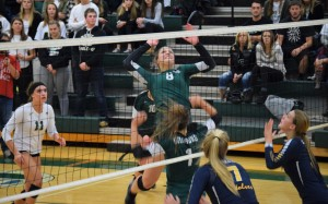 Senior Mallorie Berriman, no. 8,  jumps to spike the ball during the district championship against Clarkston on Friday. Berriman had 11 kills in the match. Photo by Jim Newell