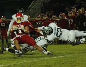 Junior Dustin Sokolowski (52) pulls down Romeo's running back for a loss in the first quarter.  Photo by Joe St. Henry