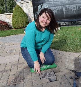 Alana Hart places a commemorative stone honoring her late father, Alan C. Hart, at the Veterans Memorial.