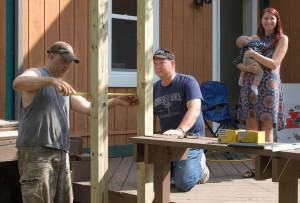 Lake Orion Police Officers Lt. Harold Rossman (right) and Reserve Officer Frank Scarpaci rebuild the Biton's back porch as Ivette and 5-month-old Gabriel watch. Photo by Susan Carroll.