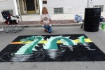 Sheila Serio came to the Dragon on the Lake festival with her two daughters, Hope and Faith, and competed in the  Chalk Art Challenge. Both Hope and Faith won awards for their chalk art drawings, but Sheila's dragon swimming through dark waters cannot be overlooked in its vivid depiction.
