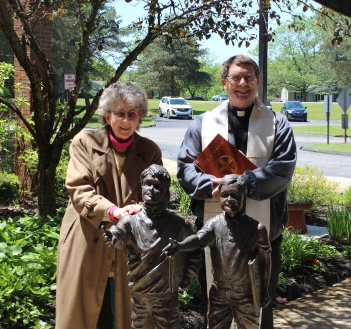 St. Joseph priest blesses Orion Twp. Public Library statue created by local sculptor